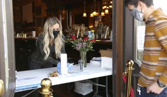 In this Saturday, April 18, 2020 photo, Golden Era bartender Jesse Giardina wears a mask and gloves as a precaution against the coronavirus as she serves customers through the entrance of the building in downtown Nevada City, Calif. (Elias Funez/The Union via AP)