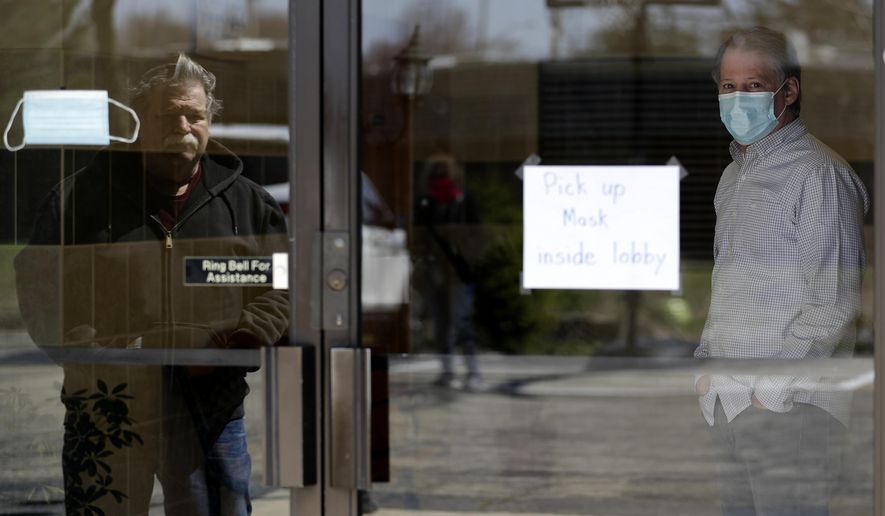 Lakewood Chapel Pastor John Elleson, right, waits for people at the church in Arlington Heights, Ill., Saturday, April 18, 2020. The church is giving away faces masks during the coronavirus pandemic. (AP Photo/Nam Y. Huh)
