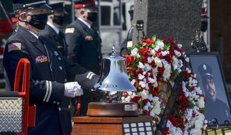 Terre Haute Fire Department Capt. Russell Feuquay rings the ceremonial bell during the funeral of firefighter John Schoffstall on Saturday, April 18, 2020, at West Vigo High School in West Terre Haute, Ind. Schoffstall died April 11 from COVID-19 complications. (Austen Leake/The Tribune-Star via AP)