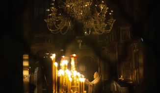 A woman lights a candle during a religion service celebrating Orthodox Easter at the Rogozhsky spiritual center of the Russian Orthodox Old-Rite Church in Moscow, Russia, late Saturday, April 18, 2020. For Orthodox Christians, this is normally a time of reflection, communal mourning and joyful release, of centuries-old ceremonies steeped in symbolism and tradition. But this year, Easter, by far the most significant religious holiday for the world's roughly 300 million Orthodox, has essentially been cancelled. (AP Photo/Alexander Zemlianichenko Jr)