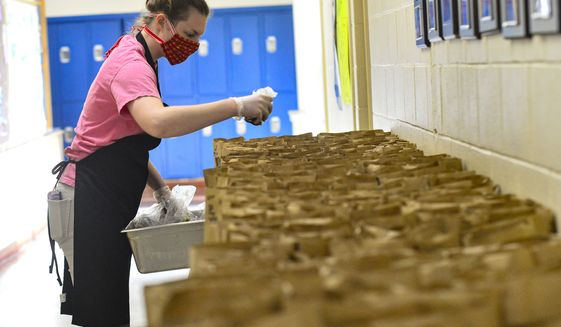 Emma Griffith helps fill brown bags with food items at Twin Vally Middle High School, in Whitingham, Vt., that will be delivered to children around the community on Monday, April 20, 2020. (Kristopher Radder/The Brattleboro Reformer via AP)