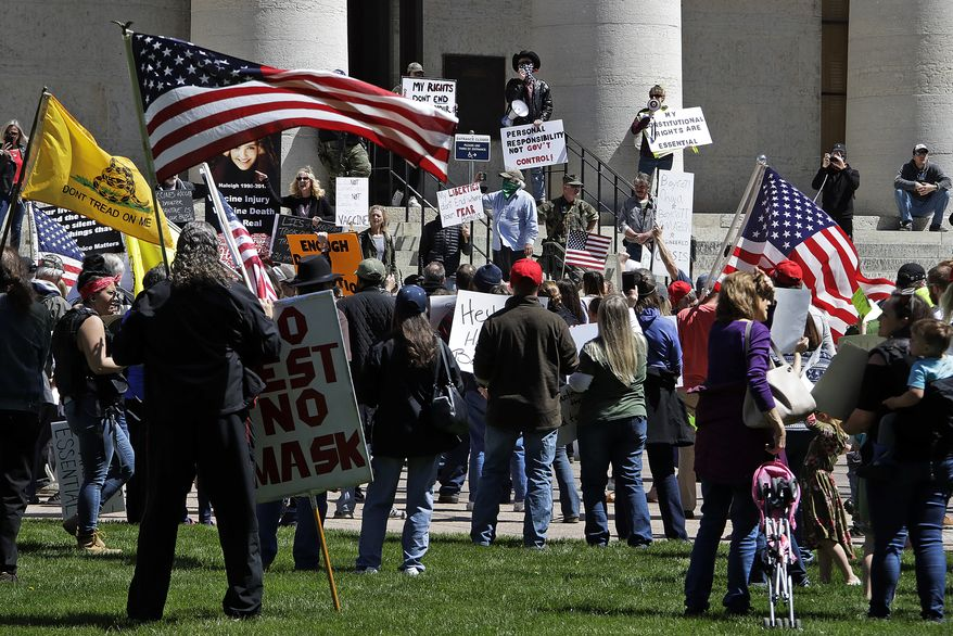 Protesters gather outside of the Ohio State House in Columbus, Ohio on April 20, 2020, to protest the stay home order that is in effect until May 1. (AP Photo/Gene J. Puskar)
