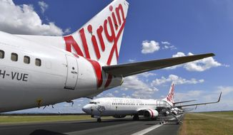 In this April 7, 2020, photo, grounded Virgin Australia aircraft are parked at Brisbane Airport in Brisbane, Australia. Virgin Australia, the nation's second-largest airline, announced Tuesday, April 21, 2020, it had entered voluntary administration as it seeks to strengthen its finances amid a debt crisis. (Darren England/AAP Image via AP)