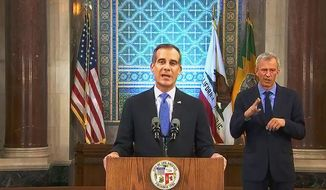 This photo from streaming video provided by the Office of Mayor Eric Garcetti shows Los Angeles Mayor Eric Garcetti giving his annual State of the City speech in an otherwise empty City Hall council chamber Sunday, April 19, 2020. He said thousands of Los Angeles city workers must take 26 furlough days, the equivalent of a 10 percent pay cut, over the course of the next fiscal year as the nation's second-largest city deals with the economic fallout from the COVID-19 crisis. Garcetti warned of an economic blow far worse than the 2008 recession, when city leaders laid off hundreds of workers and eliminated thousands of jobs. (Office of Mayor Eric Garcetti via AP)
