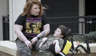 In this Thursday, April 2, 2020 photo, Anna Hauser sits with her son Xavier, 14 in the courtyard of their Madison, Wis., apartment complex.  (Steve Apps/Wisconsin State Journal via AP)