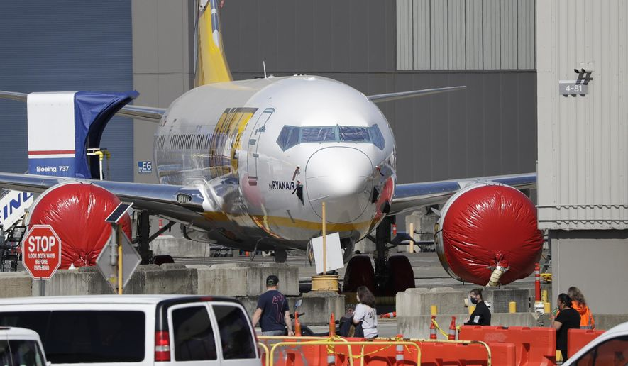 Workers walk near a Boeing 737 jet at a Boeing production plant Monday, April 20, 2020, in Renton, Wash. Boeing this week is restarting production of commercial airplanes in the Seattle area, putting about 27,000 people back to work after operations were halted because of the coronavirus. (AP Photo/Elaine Thompson)