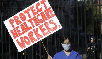 Doctor Meenal Viz holds a banner as she protests outside Downing Street in London, as the country is in lockdown to help curb the spread of the coronavirus, Sunday, April 19, 2020. The doctor who is pregnant protested about the lack of PPE and protection for NHS health workers. (AP Photo/Kirsty Wigglesworth)