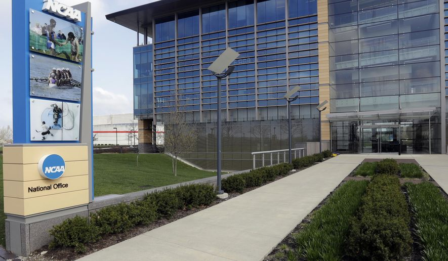 In this is an April 25, 2018, file photo, NCAA headquarters in Indianapolis is viewed. College sports programs are already being cut and more are likely on the chopping block. The coronavirus pandemic has triggered fears of an economic meltdown on campuses around the country. The cancellation of the NCAA men's basketball tournament cost schools $375 million and more losses are expected, especially if football season is disrupted in the fall. (AP Photo/Darron Cummings, File)  **FILE**