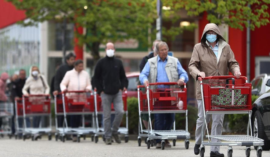 People wearing protective masks queue up to go in a garden store in Munich, Germany, Monday, April 20, 2020. The German government has moved to restrict freedom of movement for people, in an effort to slow the onset of the COVID-19 coronavirus. (AP Photo/Matthias Schrader)