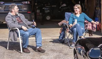 Jay and Rachel Bishop enjoy a beverage in the sun in their driveway in Auburn, on Sunday afternoon, April 19, 2020. Both are essential workers and consider themselves lucky to have jobs, knowing that many people are struggling. Rachel is happy to have a down day at home and finds the constant vigilance of having to be aware of preventing contamination, wearing masks, and sanitizing everything to be exhausting. (Andree Kehn/Sun Journal via AP)