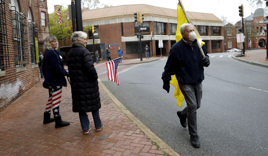 A man carries a flag as he walks by two protestors gathered at Church Circle, Monday, April 20, 2020, in Annapolis, Md. Only a few people showed up to protest and call for the state government to reopen amidst the coronavirus outbreak. Over the weekend, many protestors riding on vehicles flooded the circle in efforts to get government to reopen the state. (AP Photo/Julio Cortez)
