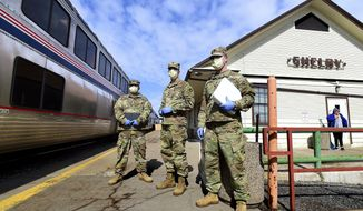 This photo taken April 14, 2020, shows Army National Guard soldiers waiting to check Amtrak passengers as Shelby, Mont., struggles with three of the seven coronavirus deaths in Montana. From left, Sgt. Willie Nesmith, Spec. Trevor Dodson and Spec. Robert Swensen meet the eastbound Empire Builder. (Larry Mayer/The Billings Gazette via AP)