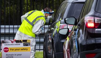 Medical personnel from Montgomery County, Md., check patients arriving for COVID-19 drive-in testing in Silver Spring, Md., Tuesday, April 21, 2020. (AP Photo/Manuel Balce Ceneta) ** FILE **