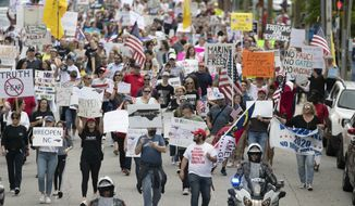 Protesters from ReOpenNC fill Lane Street as they march calling on North Carolina Gov. Roy Cooper to ease COVID-19 restrictions due to economic concerns on Tuesday, April 21, 2020 in Raleigh, N.C.  (Robert Willett/The News & Observer via AP)
