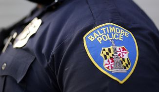 FILE - This March 31, 2016, file photo shows a shoulder patch of a Baltimore Police Department officer in Baltimore. Lawyers for the Baltimore police told a federal judge on Tuesday, April 21, 2020, that plans for camera-equipped planes to conduct aerial surveillance of the city should proceed, saying the crime-fighting tactic is constitutional despite the objections of civil liberties advocates. (AP Photo/Patrick Semansky, File)