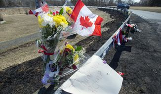 A memorial pays tribute to Royal Canadian Mounted Police Constable Heidi Stevenson, a mother of two and a 23-year veteran of the force, along the highway in Shubenacadie, Nova Scotia, on Tuesday, April 21, 2020. Canadian police are investigating at 16 crime scenes after a weekend rampage by a gunman disguised as a police officer left at least 18 dead, including Stevenson, and homes in smoldering ruins in rural communities across Nova Scotia. (Andrew Vaughan/The Canadian Press via AP)