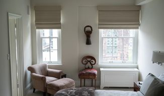 This photo provided by interior designer Carolyn DiCarlo shows a bedroom designed by DiCarlo in New York. DiCarlo created the serene bedroom for the client by combining soft colors, the harmonic forms of African art and a Biedermeier chair, and a cozy reading chair by the window that is bathed in gentle afternoon light. (Adam DiCarlo/Carolyn DiCarlo via AP)