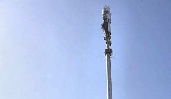 In this Tuesday, April 14, 2020 file photo, a view of a cell tower after a fire, in Dagenham, England. Dozens of European cell towers have been destroyed in recent arson attacks that officials and wireless companies say are fueled by groundless conspiracy theories linking new 5G mobile networks and the coronavirus pandemic. (Stefan Rousseau/PA via AP)