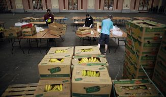 Volunteers for the Edible London food project remove the plastic packaging and check the quality of donated bananas to be put in food packs and delivered to residents who need it in the Haringey Council area, at a hub setup as a result of coronavirus inside the Alexandra Palace venue, in north London, Tuesday, April 21, 2020. The highly contagious COVID-19 coronavirus has impacted on nations around the globe, many imposing self isolation and exercising social distancing when people move from their homes. (AP Photo/Matt Dunham)