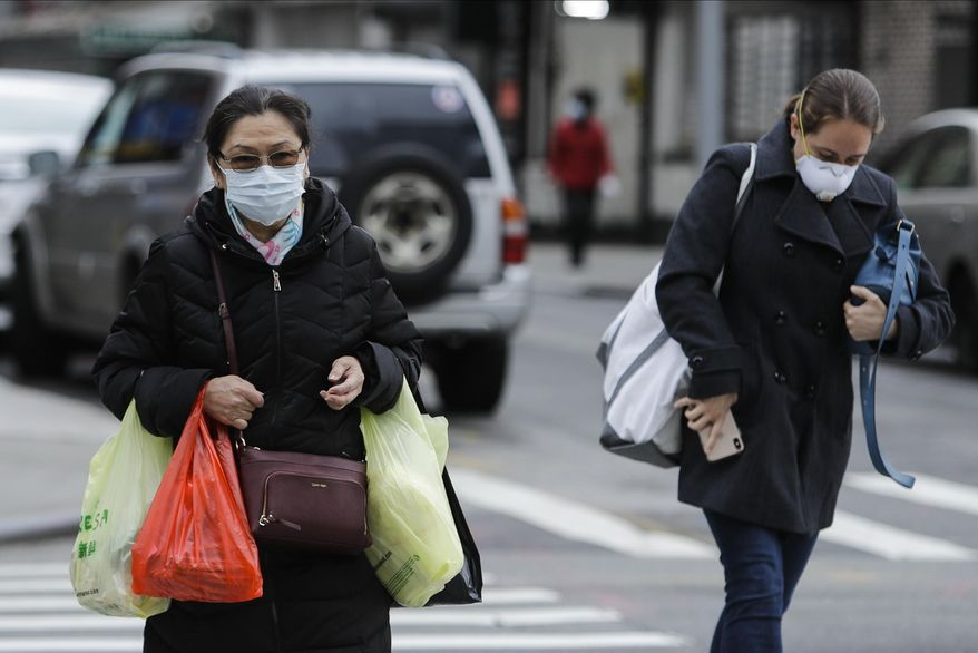 Pedestrians wearing protective masks cross Canal Street Tuesday, April 21, 2020, in New York. (AP Photo/Frank Franklin II)