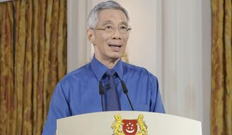 In this handout photo taken and released Tuesday, Apr. 21, 2020, by Singapore's Ministry of Communication and Information, Prime Minister Lee Hsien Loong provides an update on the COVID-19 situation in the city state. Singapore has announced that it would extend its lockdown by another four weeks after a sharp upsurge in COVID-19 cases in recent days. (Singapore Ministry of Communication and Information via AP)