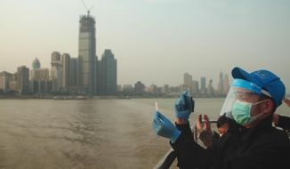 In this April 8, 2020, photo, Chen Enting, 34, snaps a photo of his ticket to commemorate his first ferry ride across the Yangtze River in Wuhan in central China's Hubei province after a 76-day quarantine ended in the city at the center of the coronavirus pandemic. The reopening of the ferry service on the Yangtze, the heart of life in Wuhan for more than 20 centuries, was an important symbolic step in official efforts to get business and daily life in this central Chinese city of 11 million people back to normal. (AP Photo/Sam McNeil)