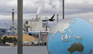 In this Tuesday, April 21, 2020, photo, a bird takes off from an Earth globe sculpture at Thea's Park in Tacoma, Wash., with the WestRock Paper Mill in the background. Wednesday is the 50th anniversary of Earth Day, an observance that helped spur activism against air and water pollution and disappearing plants and animals, but ongoing challenges remain throughout the world. (AP Photo/Ted S. Warren)