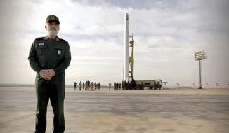In this photo released Wednesday, April 22, 2020, by Sepahnews, Gen. Amir Ali Hajizadeh, the head of the Revolutionary Guard's aerospace division stands in front of an Iranian rocket carrying a satellite in an undisclosed site believed to be in Iran's Semnan province. The Guard said Wednesday it put the Islamic Republic's first military satellite into orbit, dramatically unveiling what experts described as a secret space program with a surprise launch that came amid wider tensions with the United States. (Sepahnews via AP)