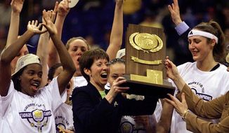 In this April 1, 2001, file photo, Notre Dame coach Muffet McGraw, center, holds up the National Championship trophy after Notre Dame defeated Purdue 68-66 for the 2001 Women's Final Four Championship in St. Louis. At left is Imani Dunbar and Ruth Riley is at right. McGraw abruptly retired Wednesday, April 22, 2020, stepping down from Notre Dame after a Hall of Fame coaching career that includes two national championships in 33 seasons. (AP Photo/Michael Conroy, File)  **FILE**