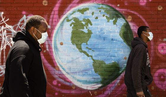 People wearing a protective face mask as a precaution against the coronavirus walk past a mural of the world in Philadelphia, Wednesday, April 22, 2020. April 22 is observed as Earth Day every year as a tool to raise ecological awareness. (AP Photo/Matt Rourke)