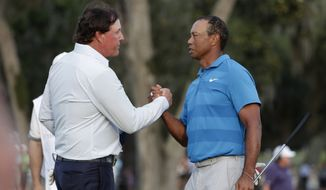 In this May 10, 2018, file photo, Phil Mickelson, left, and Tiger Woods shake hands after the first round of the Players Championship golf tournament in Ponte Vedra Beach, Fla. Woods and Mickelson are ready for a made-for-TV rematch at a time when fans are craving live action. And this time, they'll have company. Turner Sports says quarterbacks Tom Brady and Peyton Manning will join them for a two-on-two match sometime in May. Missing from the announcement were such details as when and where the match would be played, except that tournament organizers would work with government and health officials to meet safety and health standards. (AP Photo/Lynne Sladky, File)  **FILE**