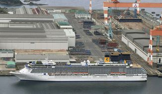 In this April 21, 2020, photo, Italian-operated cruise ship the Costa Atlantica is anchored at a port in Nagasaki, southern Japan. Japanese officials said a few dozens of crew members on the cruise ship docked have tested positive for the coronavirus on Wednesday, the day after a first case from the ship was reported. (Kyodo News via AP)