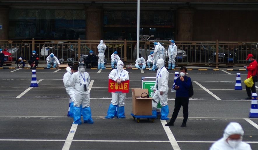 FILE - In this April 15, 2020, file photo, workers in full protective gear stand in a parking lot of the West Station in Beijing, China, as part of the team coordinating quarantine for incoming passengers from Wuhan. Getting into Wuhan was the easy part as new infections had fallen to almost zero and travel restrictions were relaxed. As a 76-day lockdown neared its end, journalists were allowed to return to the Chinese city where the coronavirus pandemic originated. But getting out was proving harder. The bureaucracy had yet to finalize how people would safely organize their return and three official documents were needed: A green health code, home neighborhood approval and a recent nucleic acid test. (AP Photo/Sam McNeil, File)