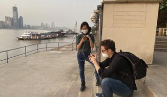 In this April 8, 2020, photo, exhausted AP staffers Olivia Zhang, center and Sam McNeil, right, rest on the banks of the Yangtze River in Wuhan in central China's Hubei province. For AP journalist Sam McNeil, getting into Wuhan was easy compared to the trials of securing a train ticket, getting nucleic tests, green codes, neighborhood approvals and submitting to electronic monitoring to find his way home to Beijing. (AP Photo/Ng Han Guan)