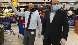 In this Sunday, April 19, 2020 photo, Majid Al Futtaim CEO Alain Bejjani, right, and store manager Arnaud Bouf, wear masks amid the coronavirus pandemic and walk through the world's busiest Carrefour supermarket in Mall of the Emirates in Dubai, United Arab Emirates. One of the biggest private employers in the Middle East hasn't yet cut salaries or laid off any of its 44,000 workers, but the pandemic is changing how Majid Al Futtaim, the company that owns and operates hundreds of grocery stores and more than two dozen malls, thinks about food security, retail and tourism. (AP Photo/Jon Gambrell)