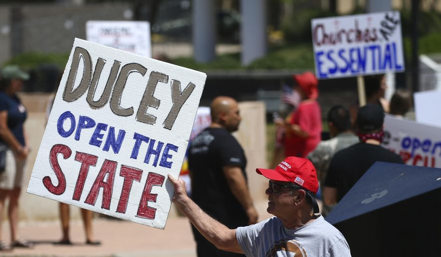 In this April 20, 2020, photo, protesters rally at the state Capitol to 're-open' Arizona against the governor's stay-at-home order due to the coronavirus in Phoenix. (AP Photo/Ross D. Franklin) **FILE**