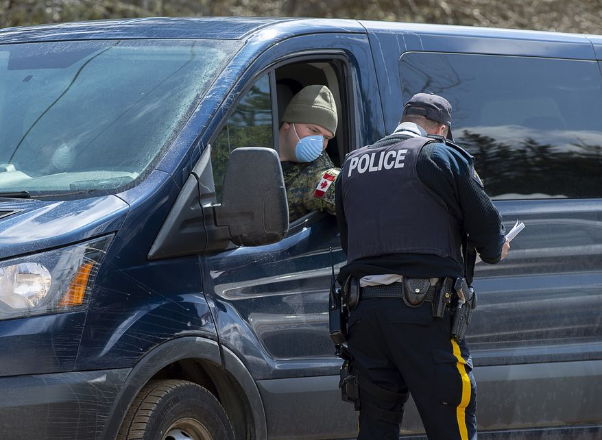A soldier talks with an RCMP officer at a checkpoint in Portapique, N.S. on Thursday, April 23, 2020. The military has provided personnel, modular tents, lights, tables, chairs and generators to a number of locations in the province. RCMP say at least 22 people are dead after a man who at one point wore a police uniform and drove a mock-up cruiser, went on a murder rampage in Portapique and several other Nova Scotia communities. (Andrew Vaughan/The Canadian Press via AP)