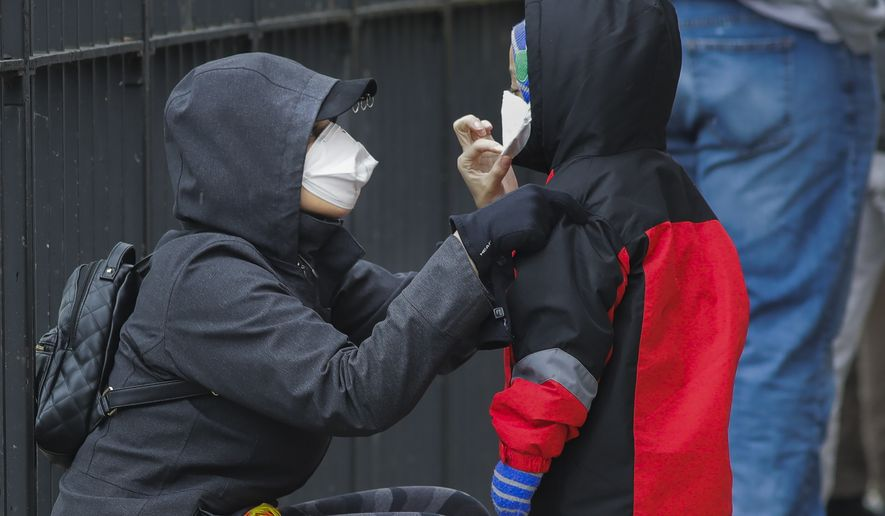 A woman adjusts her child's protective mask as they wait in line to be screened for COVID-19 at Gotham Health East New York, Thursday, April 23, 2020, in the Brooklyn borough of New York. (AP Photo/Frank Franklin II)