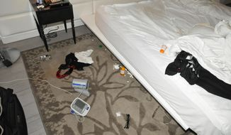 In this March 13, 2020, photo made available Wednesday, April 23, by the Miami Beach Police Department shows the hotel room where former Florida Gubernatorial candidate Andrew Gillum was found drunk and with two other men. This and other photos released Wednesday show vomit-stained and rumpled bed sheets, a box for a party light disco ball, spilled white pills on the carpet and a vial of a drug often used for erectile dysfunction. Gillum said in March that he was in Miami Beach for a wedding and did not use illegal drugs. After the hotel room encounter became public, Gillum announced he was entering a rehabilitation facility, saying he had fallen into a depression and alcohol abuse after losing his bid for governor. (Miami Beach Police Department via AP)