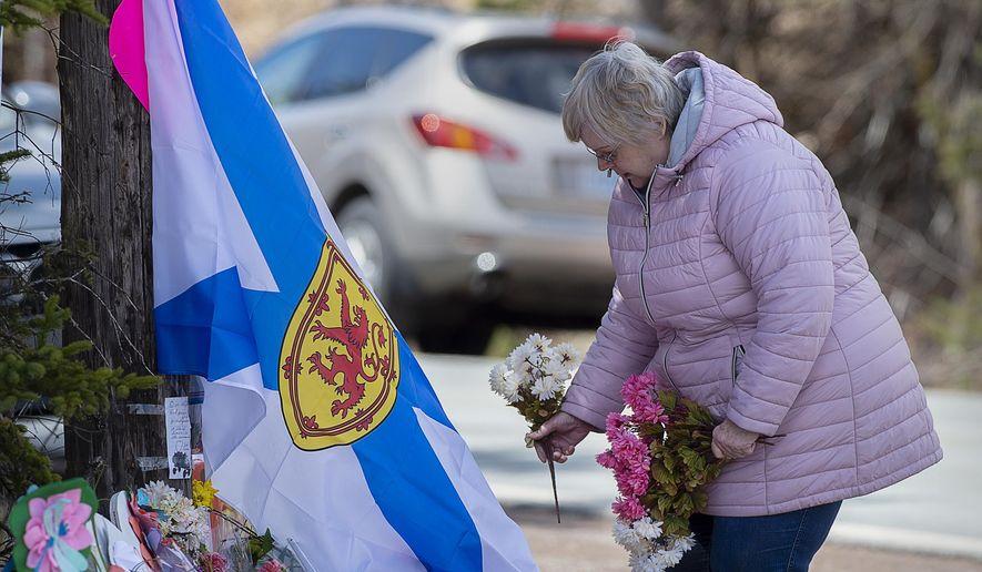 A woman pays her respects at a roadside memorial in Portapique, Nova Scotia on Thursday, April 23, 2020. Royal Canadian Mounted Police say multiple people are dead after a man who at one point wore a police uniform and drove a mock-up cruiser, went on a murder rampage in Portapique and several other Nova Scotia communities. (Andrew Vaughan/The Canadian Press via AP)