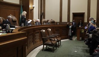New Washington Supreme Court Justice Raquel Montoya-Lewis, center right, is sworn in, Monday, Jan. 6, 2020, in Olympia, Wash. Montoya-Lewis was appointed by Gov. Jay Inslee to fulfill the remaining term of former Chief Justice Mary Fairhurst, who retired in January as she battles cancer. (AP Photo/Ted S. Warren)