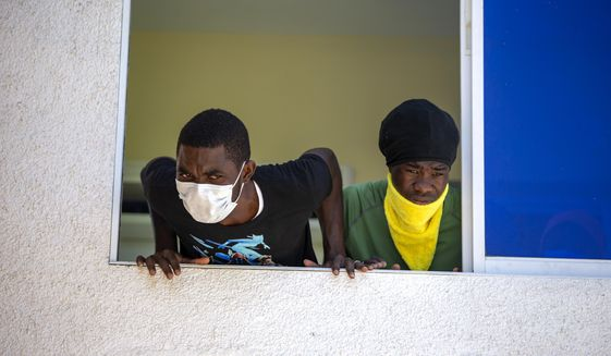 Two men who were deported from the United States and who tested positive for the new coronavirus listen to recommendations given to them by doctors, from the window of the hotel that is used to quarantine them in Tabarre, Haiti, Sunday, April 19, 2020. (AP Photo/Dieu Nalio Chery)