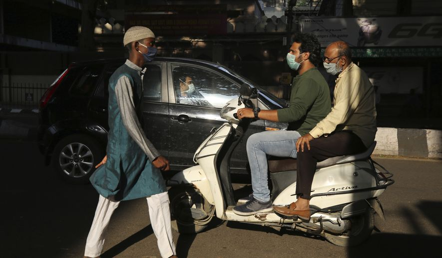 Indians commute wearing face masks as a precaution against the new coronavirus during lockdown in Bangalore, India, Friday, April 24, 2020. (AP Photo/Aijaz Rahi)