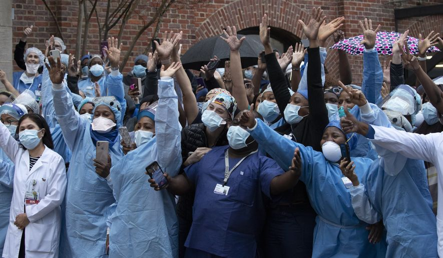 Healthcare workers react to applause at Brooklyn's Kings County Hospital Center during a 7 o'clock ceremony during the coronavirus pandemic, Friday, April 24, 2020, in New York. (AP Photo/Mark Lennihan)