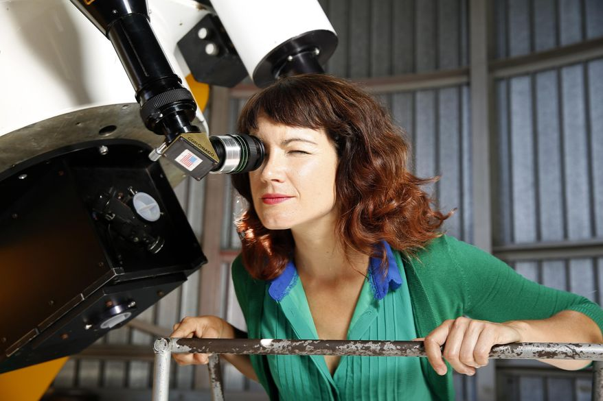 In this Aug. 5, 2015 photo, astronomer Lucianne Walkowicz looks at solar flares on the sun through a telescope at the Adler Planetarium's observatory in Chicago. Walkowicz is suing the maker of American Girl dolls, alleging the Wisconsin company stole her likeness and name to create its astronaut doll.  (Michael Tercha/Chicago Tribune via AP)