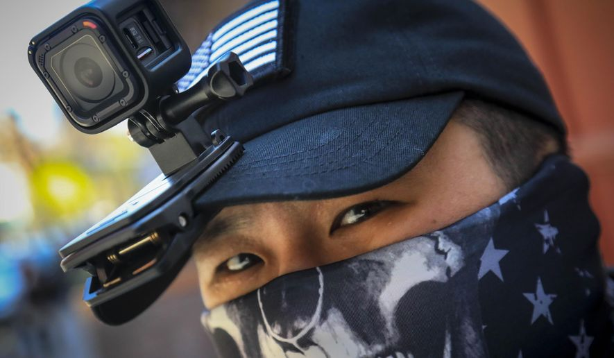 """Eddie Song a Korean American entrepreneur, arrives at his motorcycle storage garage wearing a video camera clipped to his cap and a face mask due to COVID-19, Sunday April 19, 2020, in East Village neighborhood of New York. """"I was assaulted a few months ago by someone who said that corona[virus] was created by Asians,"""" said Song. Since the assault, Song routinely wears cameras and extra padding under his jacket while walking or riding, prepared to record and intervene to stop racist attacks against Asians being blamed for COVID-19. (AP Photo/Bebeto Matthews)"""