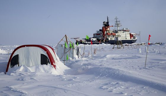 In this photo taken on Tuesday, Dec. 3, 2019 and provide by the Alfred-Wegener-Institute show the German Arctic research vessel Polarstern in the ice next to a research camp Ocean City in the Arctic region. Germany's Alfred Wegener Institute for Polar and Ocean Research says the expedition ship RV Polarstern will leave its position in the high Arctic for three weeks to rendezvous with two vessels bringing fresh supplies and crew. (Michael Gutsche/Alfred-Wegner-Institut via AP)