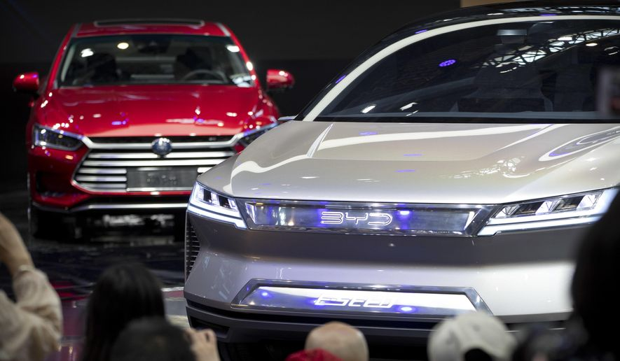 """In this April 25, 2018, photo, attendees take photos of the E-SEED electric concept car during a press conference by Chinese automaker BYD at the China Auto Show in Beijing. China is promising more subsidies to shore up plunging electric car sales amid the coronavirus pandemic but set limits that exclude Tesla's made-in-China model. Subsidies and tax breaks that were due to end this year will be extended by two years in response to """"an accumulation of unfavorable factors"""" including the virus, the Finance Ministry said Thursday, April 23, 2020. (AP Photo/Mark Schiefelbein) **FILE**"""