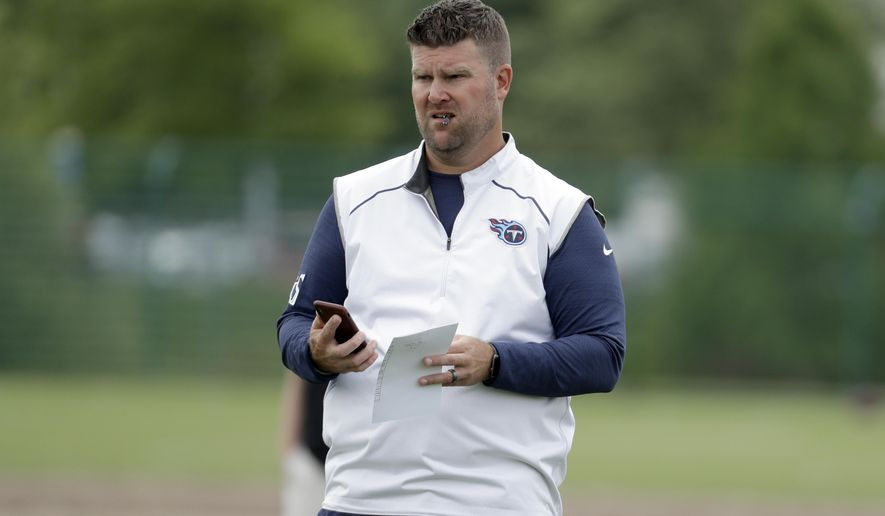 FILE - In this June 12, 2019, file photo, Tennessee Titans general manager Jon Robinson watches players during an organized team activity at the Titans' NFL football training facility in Nashville, Tenn. The 2020 NFL Draft is April 23-25.(AP Photo/Mark Humphrey, File)