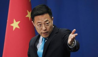 In this file photo taken Monday, Feb. 24, 2020, Chinese Foreign Ministry new spokesman Zhao Lijian gestures as he speaks during a daily briefing at the Ministry of Foreign Affairs office in Beijing. From Asia to Africa, London to Berlin, Chinese envoys have set off diplomatic firestorms with a combative defense whenever their country is accused of not acting quickly enough to stem the spread of the coronavirus pandemic. (AP Photo/Andy Wong, File)